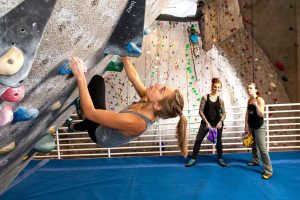 female climbing wall as two others look on